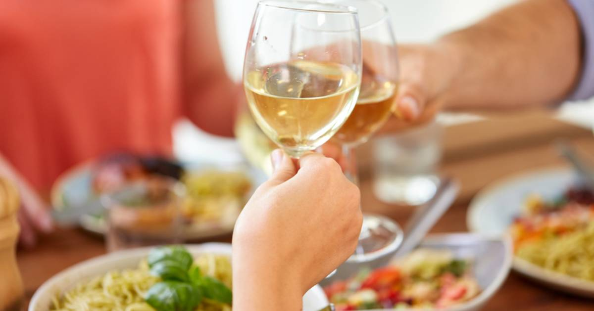 clinking wine glasses together over dinner table