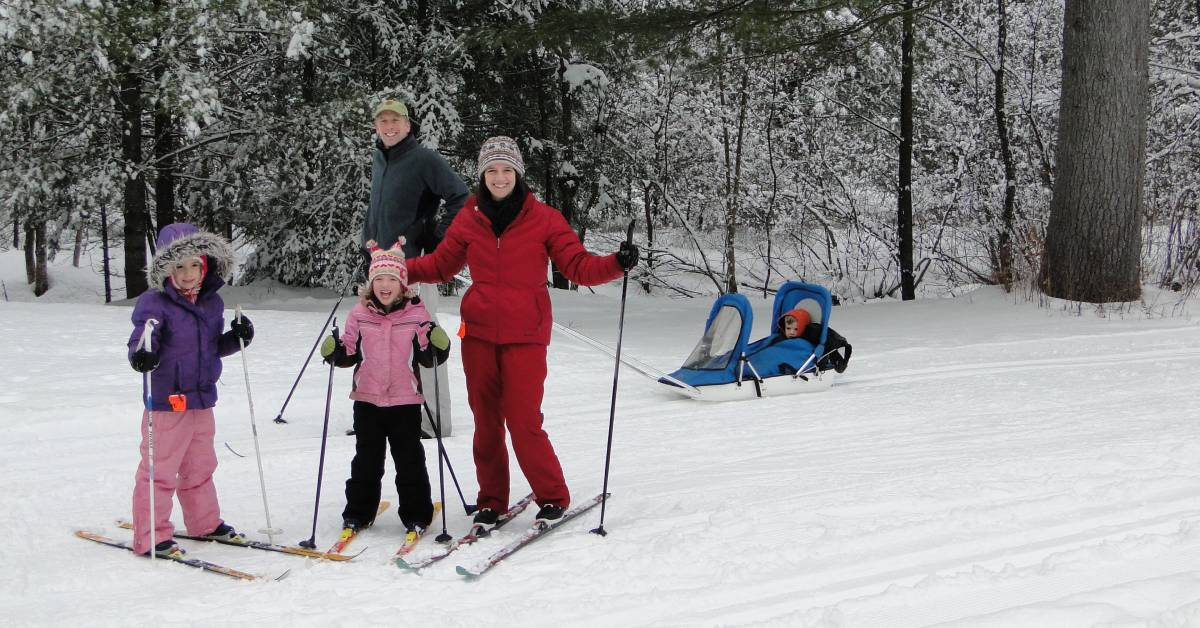 man, woman, two girls, and young boy in a sled outdoors