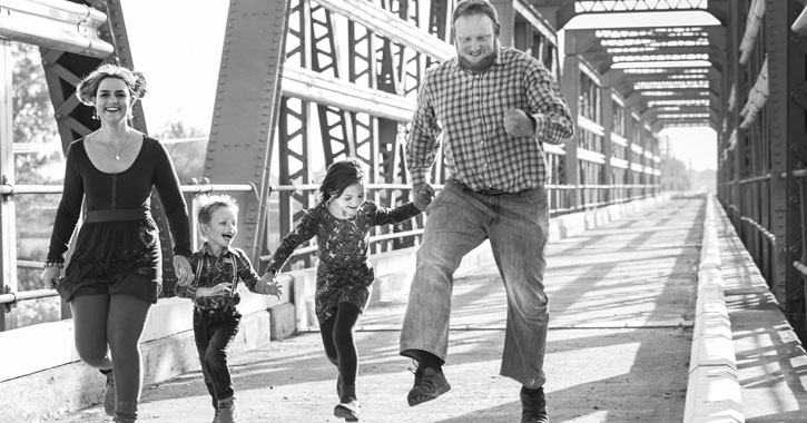 a black and white photo of parents with two young daughters skipping and laughing on a bridge