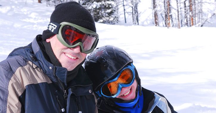 father and son in ski gear on mountain smiling at camera