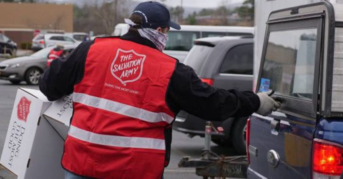man wearing salvation army vest at a car