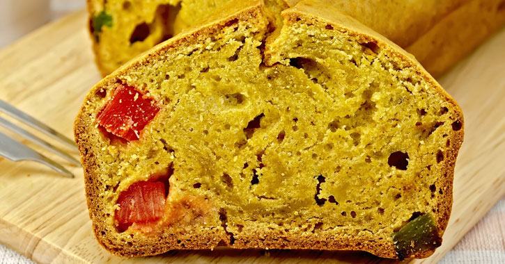 close up of a slice of fruitcake with loaf behind it and fork to the left