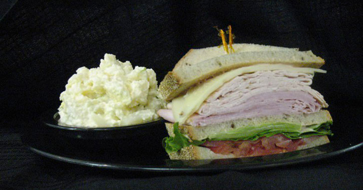 a stacked turkey, ham, cheese, lettuce, and tomato sandwich on a plate with a side of egg salad
