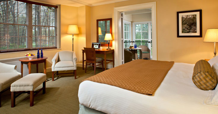 a large bed in a hotel suite with chairs and a small table and an adjoining room
