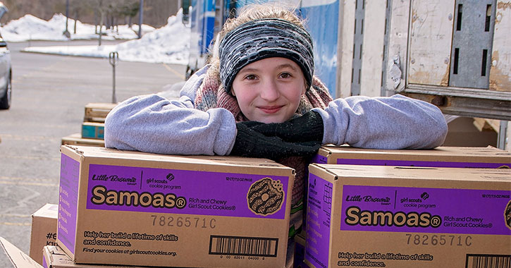 girl leaning on box of samoas cookies