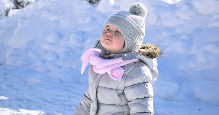 a cute little girl with a silver coat and hat and a pink scarf standing in the snow with her eyes closed