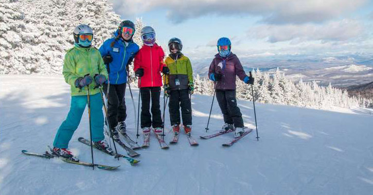 a group of people in skis at the top of the mountain