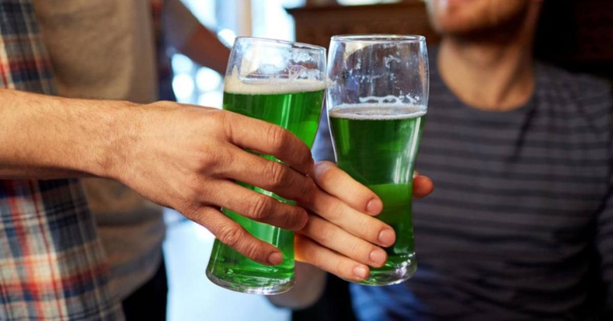 two people holding up glasses of festive green beer