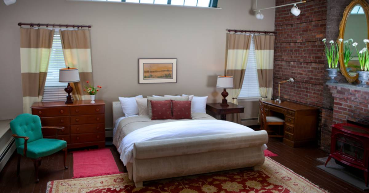 a guest room with a large bed, a green chair, a nightstand, dresser, and a red fireplace