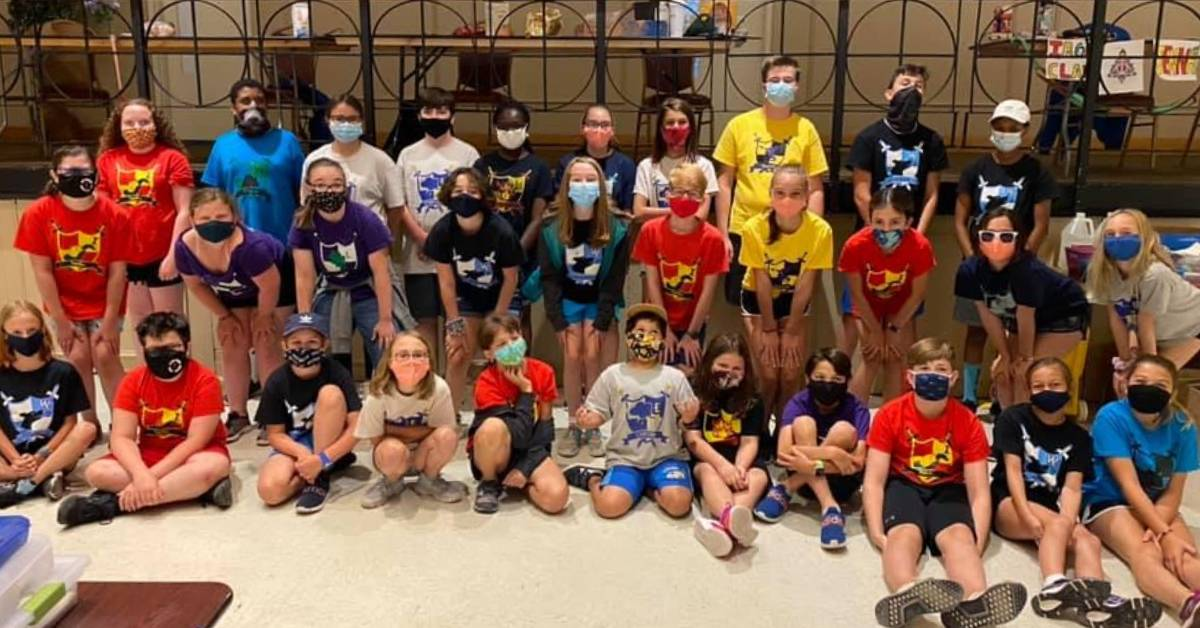 kids wearing masks in a group photo at summer camp