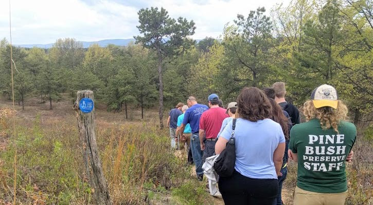 a group of hikers on a trail, the back of the last person's shirt says Pine Bush Preserve Staff