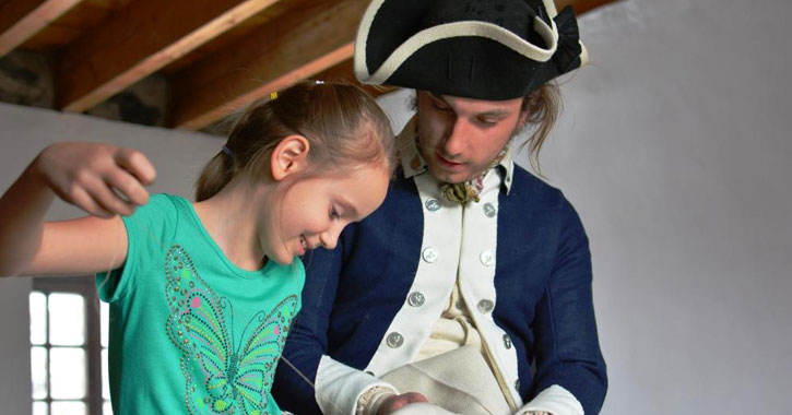 a man dressed in colonial attire showing something to a little girl