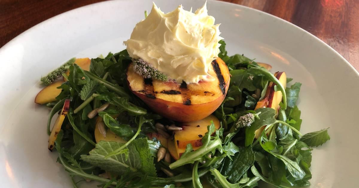 an arugula salad with peaches
