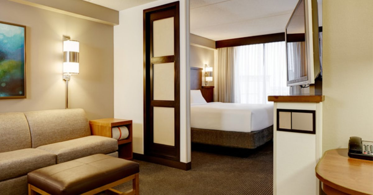 a hotel suite with a living and a sleeping area