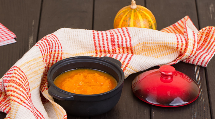 orange soup displayed with a nice blanket and a pumpkin