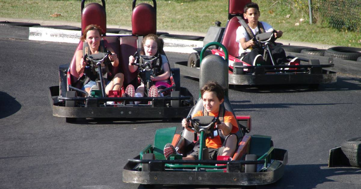 kids and a woman riding go karts