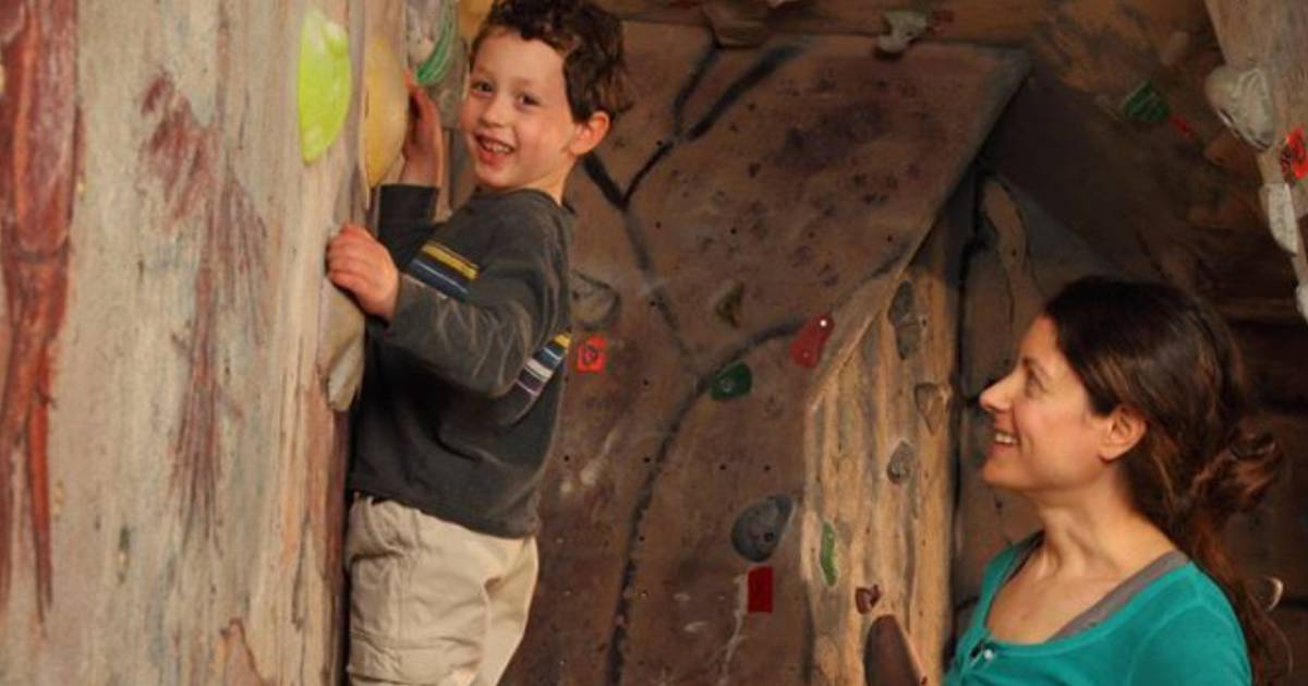 a boy rock climbing with a woman supervising