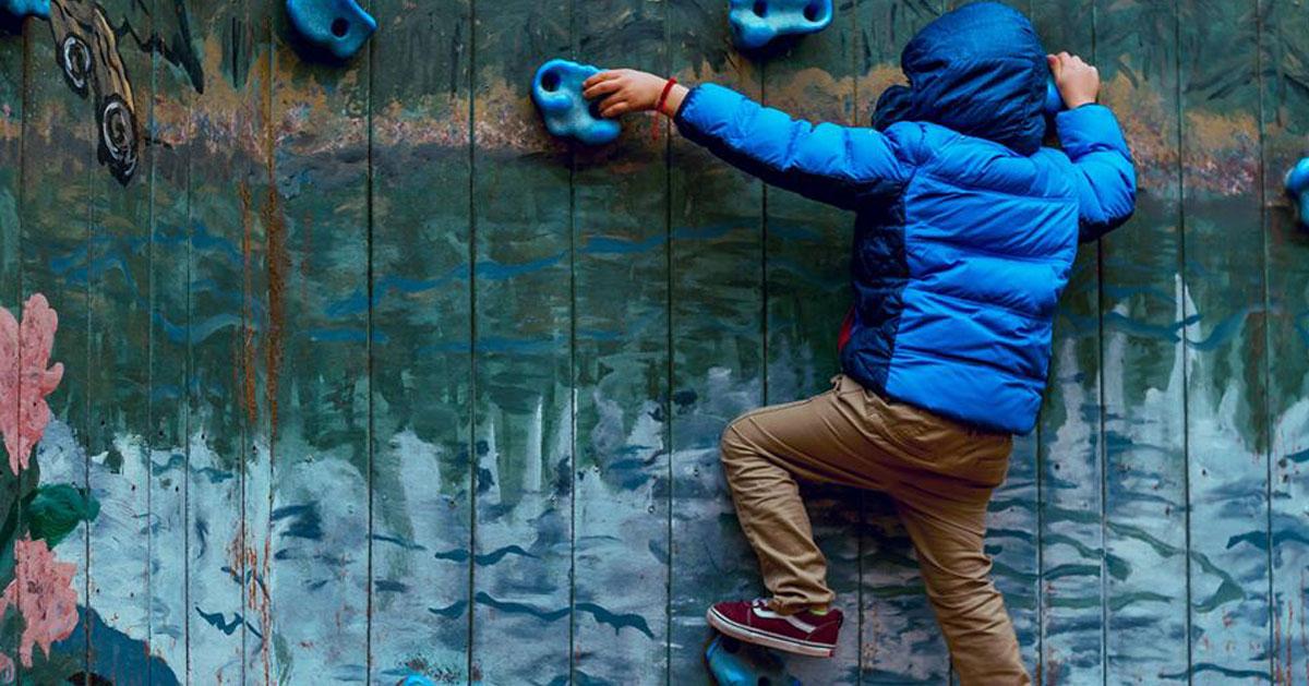 kid in blue jacket rock climbing