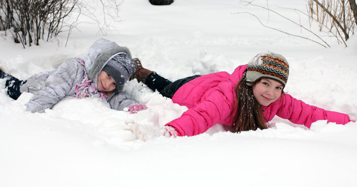 two little girls face down on their stomachs in the snow, smiling at the camera