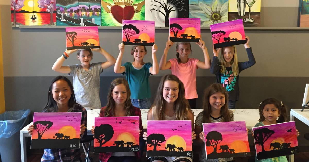 group of kids holding up their paintings of an elephant, etc.