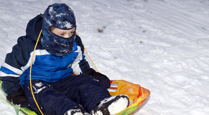 a little boy on a small sled, he's bundled up in a snowsuit and a hat that covers all his face but his eyes
