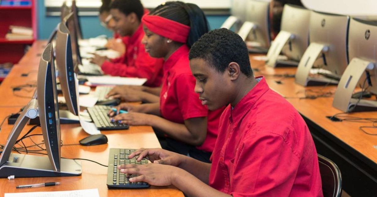 group of teenage students in red shirts at computers