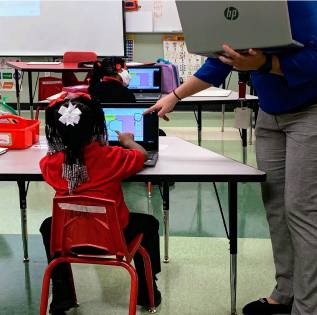 a little girl on a computer at school