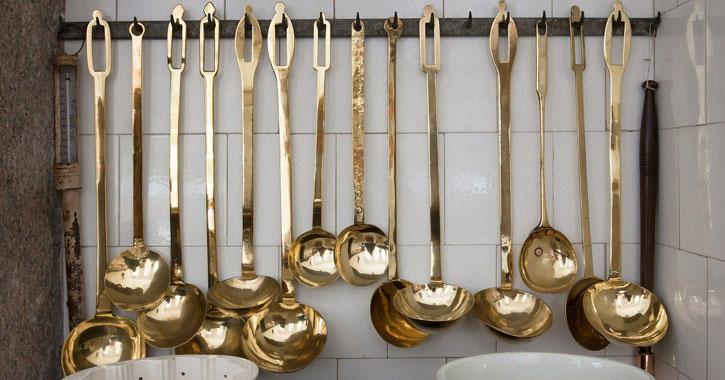 brass ladles hanging in a kitchen