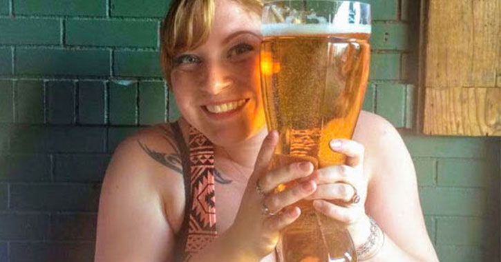 woman holding large glass of beer