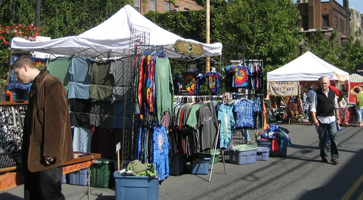 a man browsing a clothing vendor booth