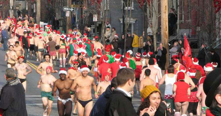 a bunch of people running, many in speedos and Santa hats