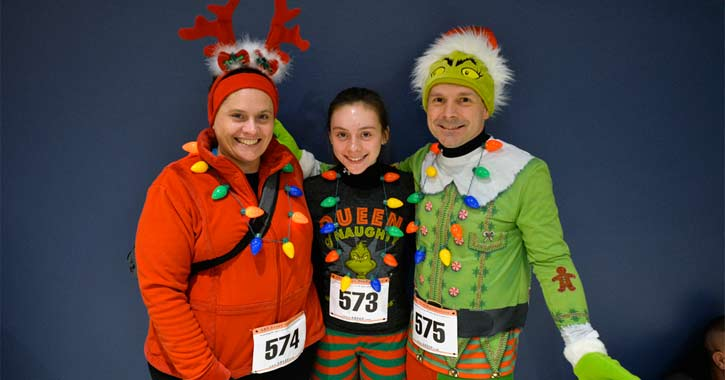 three runners posing in festive Christmas outfits
