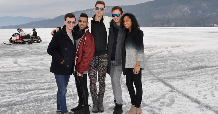 group of young people standing on the ice posing, someone snowmobiling in the background