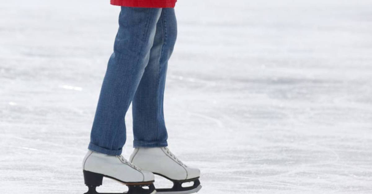 person wearing blue jeans and wearing white ice skates
