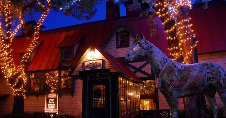 the outside of Longfellows at night with lights on the trees and a statue of a horse