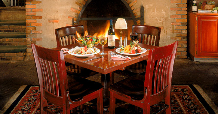 a table set up with food in a restaurant in front of a fire
