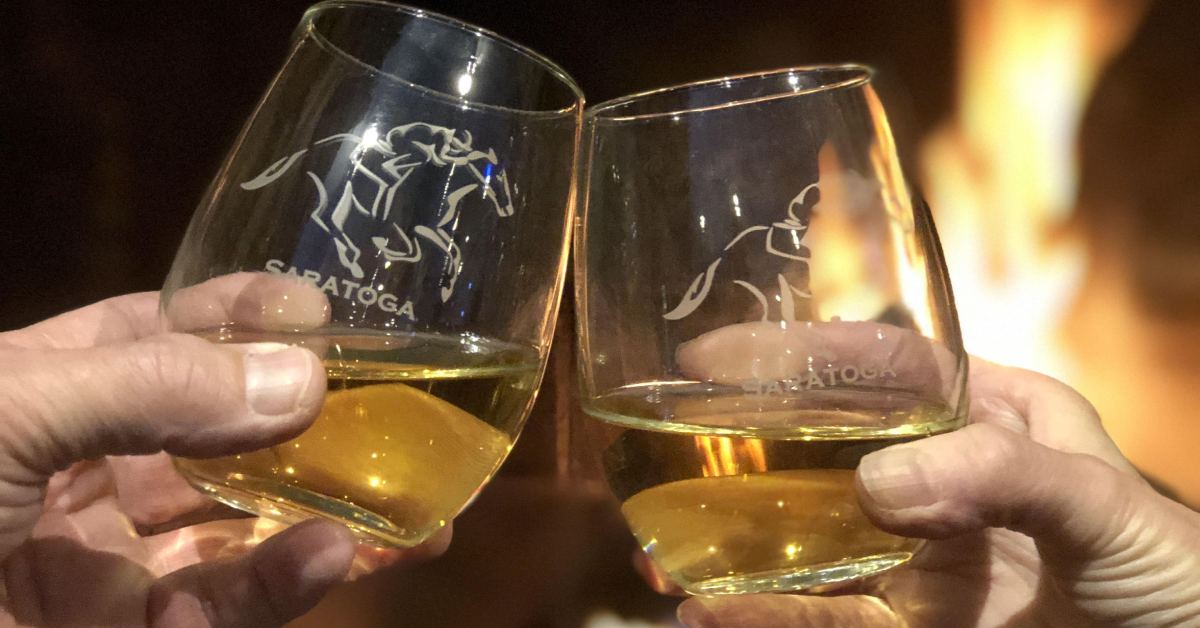 two hands holding up stemless wine glasses by a fireplace