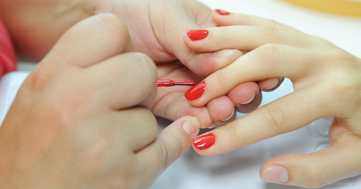 a woman's hand getting a manicure with a bright pinkish red color
