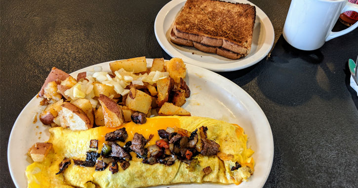 a steak and cheese omelette with toast and coffee