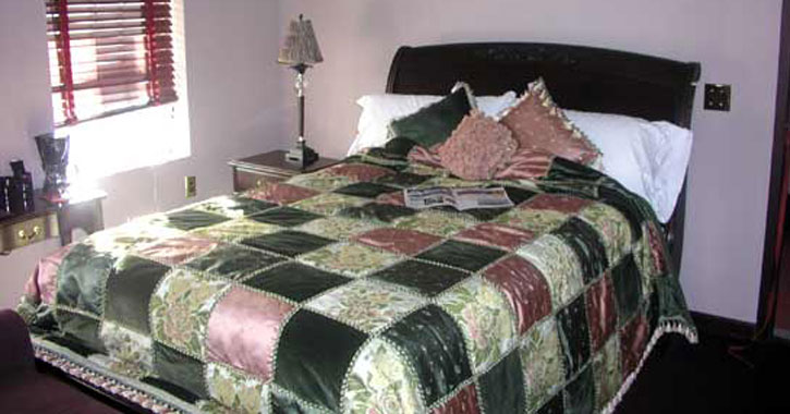 a bed with a checkered bedspread in a forest green and salmon pink design