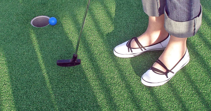 close up of a woman's shoes as she mini golfs