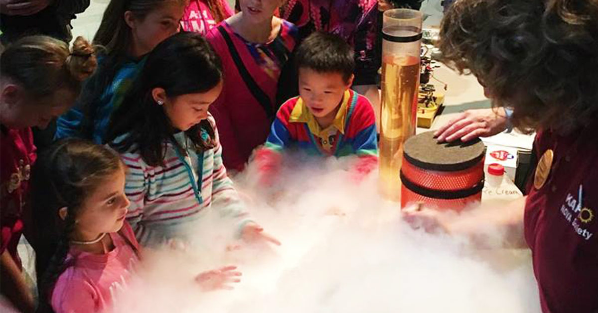 kids watching a science experiment at a museum