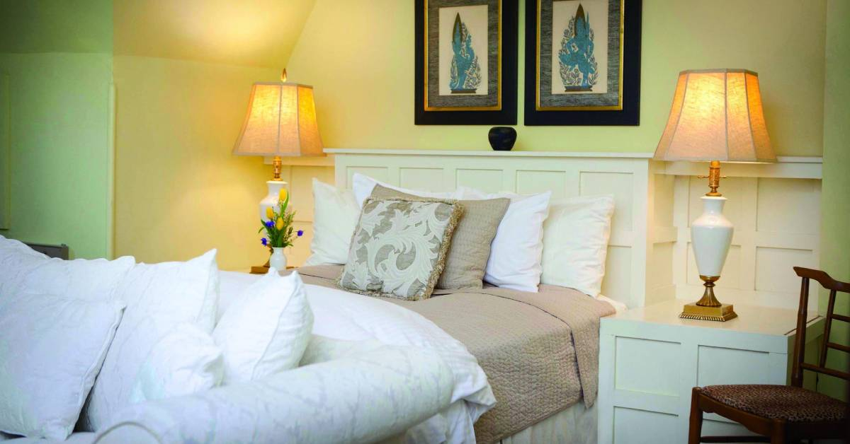 a bed with pillows and blankets, and a vase and lamp on a nearby nightstand