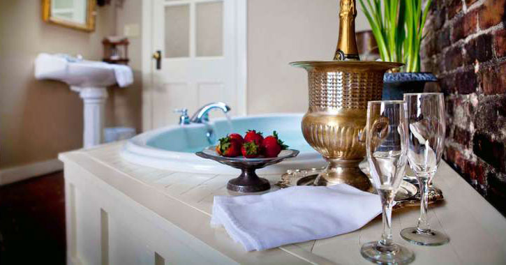 champagne, glasses, and a plate of strawberries laid out in front of a hot tub in a hotel room