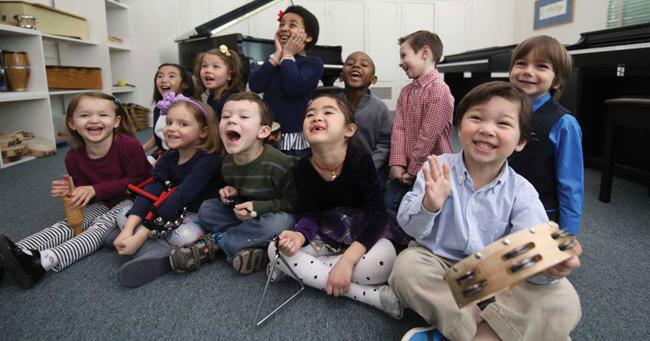 kids with musical instruments sitting on a floor, laughing