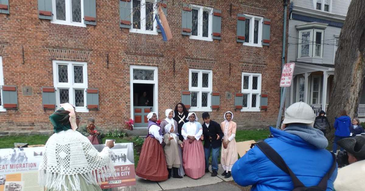 kids dressed in 19th century attire in front of the myers residence