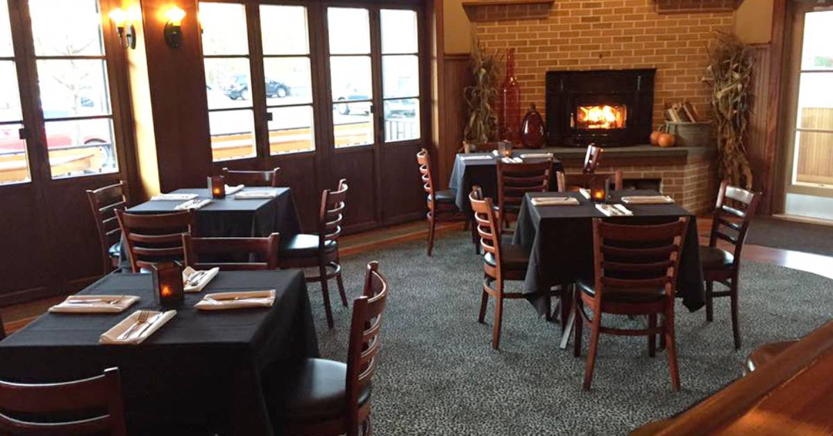 tables and a fireplace in a dining room