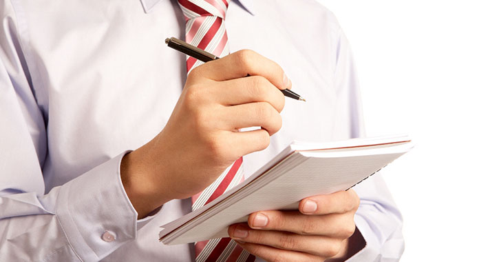 man with pen above notebook