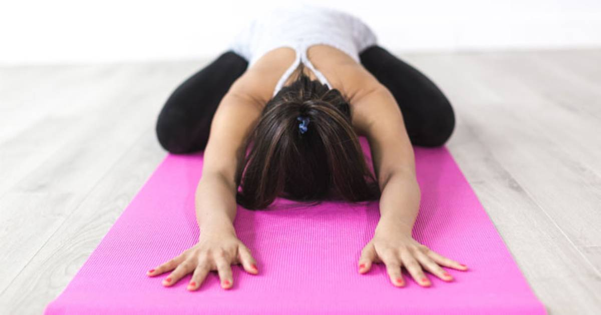 woman doing yoga on a pink mat