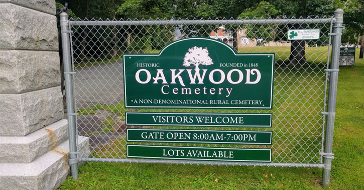 sign on a fence for Oakwood Cemetery